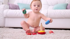 Cute little kid in nappy sits on carpet and plays with pyramid Stock Footage