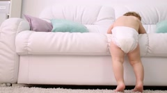 Back of kid in diaper climbing down from white sofa at home Stock Footage