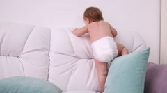Little kid in diaper climbs on white sofa with pillows at home Stock Footage