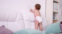 Little kid in diaper plays with toys on white sofa with pillows Stock Footage
