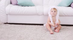 Barefoot little kid in white soft pants and hat sits on carpet Stock Footage