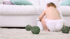Baby in white soft hat sits on carpet with balls near sofa Stock Footage