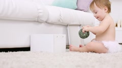 Barefoot baby in pants plays with ball near white box at home Stock Footage