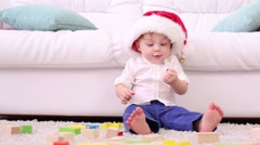 Cute little kid in red cap sits near couch among tinker toys Stock Footage