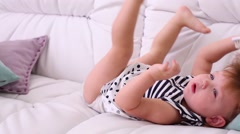 Barefoot little girl in dress raises legs on white couch Stock Footage