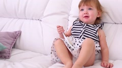 Barefoot little girl in dress sits on white couch with brush Stock Footage