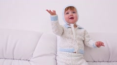 Little baby in hats and knitted suit sits on white sofa at home Stock Footage