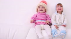 Two little kids in hats sit on back of white sofa at home Stock Footage