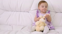 Little baby in dress with toy sits on white sofa at home Stock Footage
