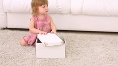 Little girl sits near white box on soft carpet and stands up - stock footage