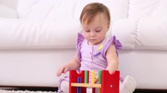 Little girl in dress plays with toy for development of thinking - stock footage