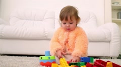 Cute little girl sits on carpet and plays with tinker toys Stock Footage