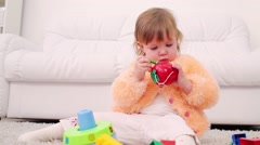Pretty little girl sits on carpet and holds toy apple with worm Stock Footage