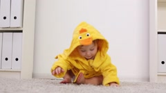 Little cute baby in yellow robe stands and leaves on white carpet Stock Footage