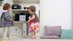 Two happy little girls stand near shelves with music center Stock Footage