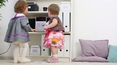 Two little girls stand near shelves and look at stereo system Stock Footage