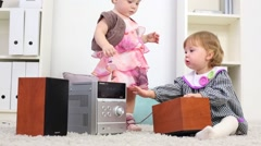 Two little girls play stereo system on carpet in room at home Stock Footage