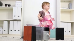 Little girl in dress stands near music system on carpet in room Stock Footage