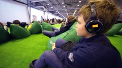 Boy in headphones looks at big screen at conference - stock footage