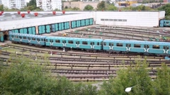 Two city underground trains move in depot gates at summer day Stock Footage