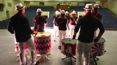 Back of musical group of thirteen people playing on drums Stock Footage