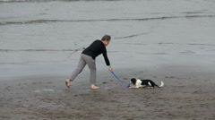 WOMAN THROWS BALL FOR DOG, SANDSEND, NORTH YORKSHIRE, ENGLAND Stock Footage