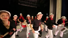 Musical group of thirteen people play drums on stage in rehearsal Stock Footage