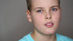 Portrait of teen boy in blue T-shirt smiling in studio Stock Footage