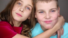 Cute little girl and boy teen hugging and smiling in studio Stock Footage