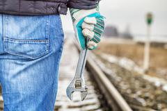 Stock Photo of Man with adjustable wrench on the railroad