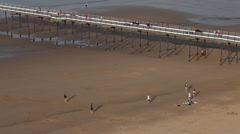 PEOPLE WALKING ON PIER & BEACH, SALTBURN-BY-THE-SEA, NORTH YORKSHIRE, ENGLAND Stock Footage
