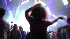 Back of woman dancing in crowd in night club during big party Stock Footage