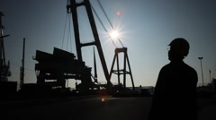 Back Lit Silhouette of Engineer in Shipyard with Floating Crane Stock Footage