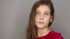 Portrait of little girl looking up and at camera in studio Stock Footage