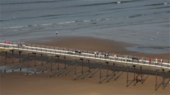 PEOPLE WALKING ON LONG PIER, SALTBURN-BY-THE-SEA, NORTH YORKSHIRE, ENGLAND Stock Footage