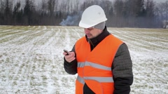 Forest inspector talking on a phone near smoke in the woods Stock Footage