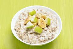 Porridge with apple and bananas slices Stock Photos