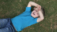 Four year old child lying on grass laughing and being tickled by mother Stock Footage
