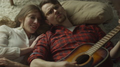 Young Happy Smiling Couple are Laying on the Floor and Playing Guitar at Evening Stock Footage