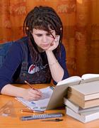 Girl with dreadlocks writes in the workbook alongside textbooks Stock Photos