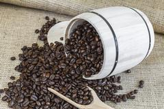 Scattered roasted coffee beans by a wooden barrel Stock Photos