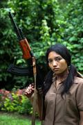 Asian woman holding a submachine gun - stock photo