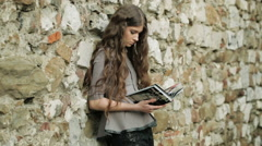 Naturally Beautiful Young Woman Reads Fashion Magazine Leaning On Stone Wall Stock Footage