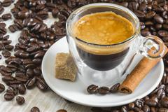 fresh espresso coffee in transparent glass with golden crema - stock photo