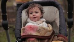 Baby in stroller waiting for mom and dad. Blurred parents collecting firewood. Stock Footage