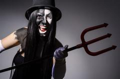 Satana woman with pitchfork and facemask Stock Photos