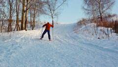 Cross-country skiing in sunny day. Moving up on the hill in the park Stock Footage