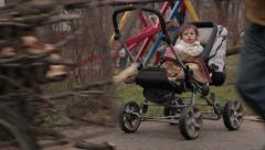 Parents collecting firewood,kids playing on swing,baby in stroller.Gypsy family. Stock Footage
