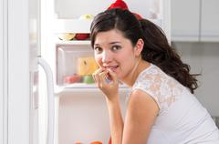 Young beautiful woman searching for food in the fridge Stock Photos