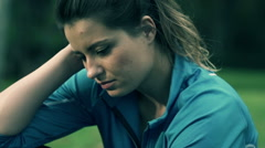 Stock Video Footage of Portrait of sad female jogger sitting in park HD